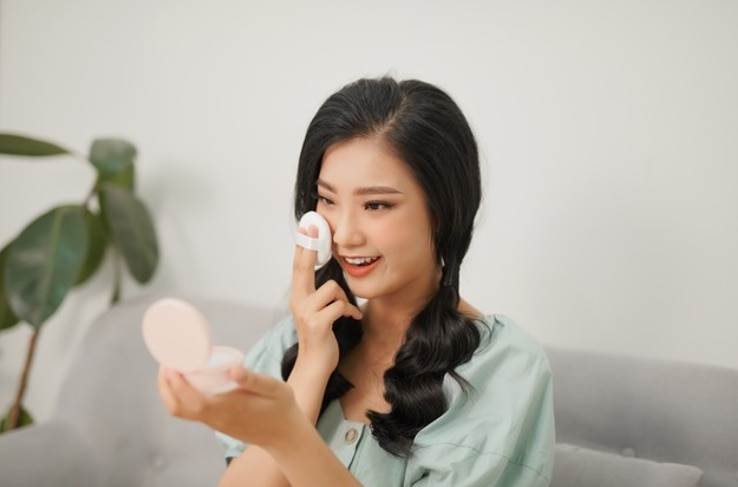 Asian Woman Applying Cushion Foundation to her face