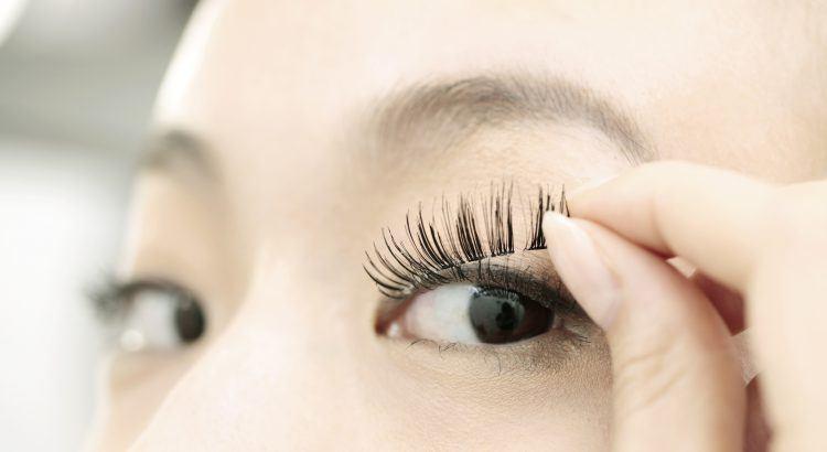 Asian girl putting false lashes to her eyelashes