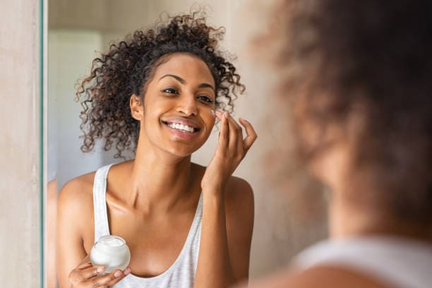 Young African woman woman applying facial moisturizer to her face