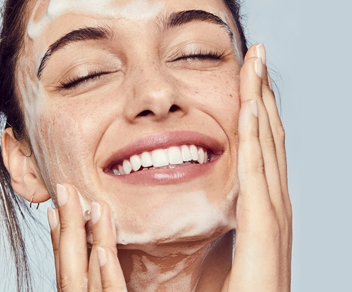 Woman applying facial cleanser to her face