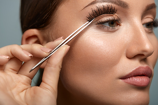 Woman with hooded eyes putting false lashes