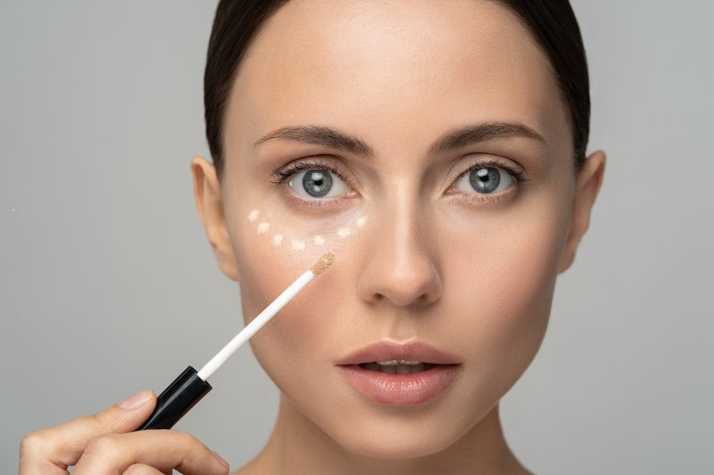 Woman with natural makeup applying concealer