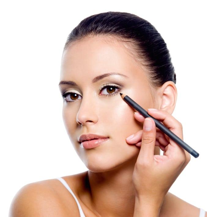 woman applying eyeliner on eyelid with pencil