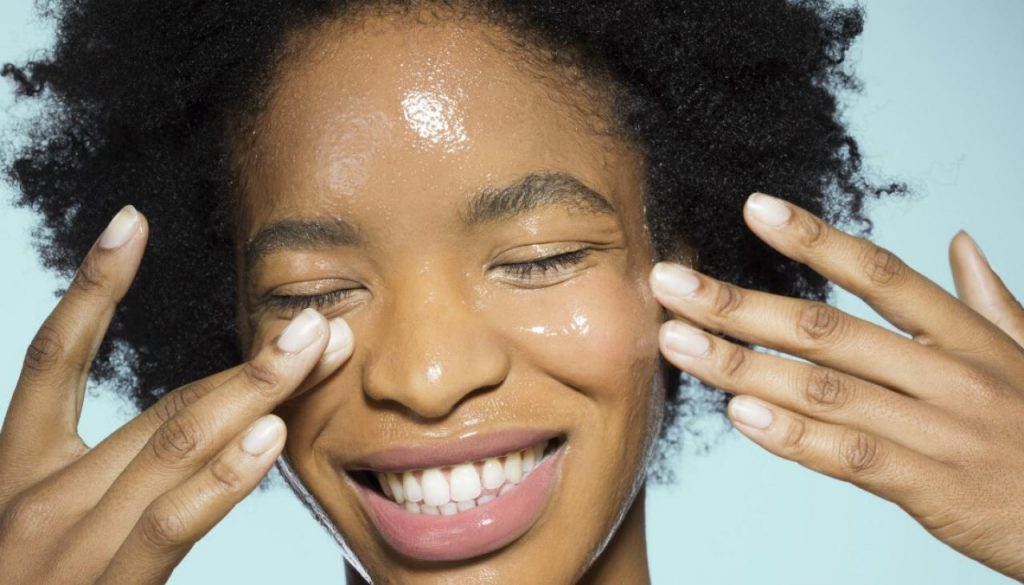 Young woman applying oil cleanser