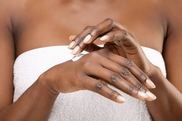 african woman applying lotion to her hands