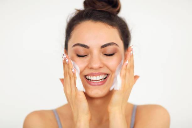 beautiful woman washing her face with face wash foam