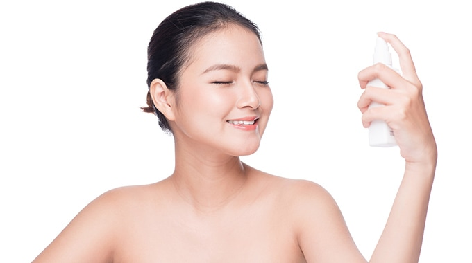 woman applying face mist to face