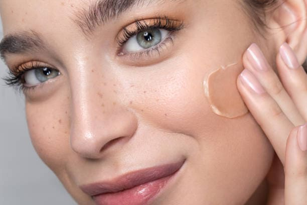 young woman applying foundation to her face